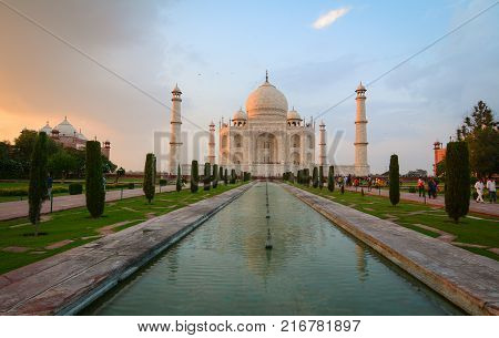 Agra India - Jul 13 2015. People walking at Taj Mahal at sunset in Agra India. The palace was commissioned in 1632 by Shah Jahan to house the tomb of his favourite wife.