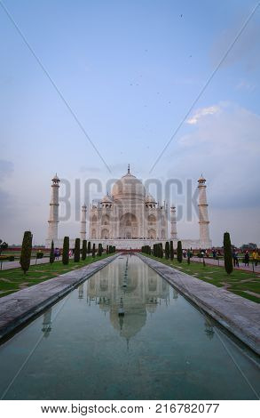 Agra India - Jul 13 2015. People visit Taj Mahal at sunset in Agra India. The palace was commissioned in 1632 by Shah Jahan to house the tomb of his favourite wife.