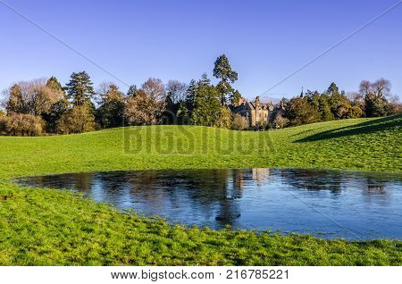 A country mansion set amongst trees with a frozen pond in the foreground