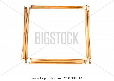 Wooden knitting needles arranged as borded frame isolated on white background