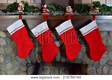 4 Christmas stockings hanging on stone fireplace with no names and not stuffed