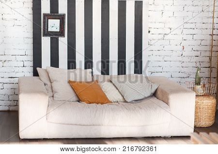 Loft modern interior with white brick wall, black stripes and sofa in front