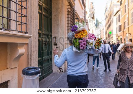 ROME ITALY - April 4 2017: Back view of florist or flower seller walking in the street of Rome on his way of deliver plenty of flowers bouquet.