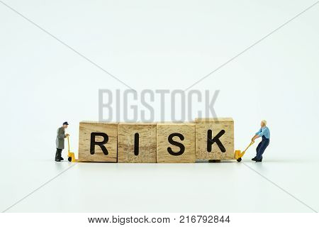Investement Risk management concept with miniature workers small figure help using hand manual forklift to move wooden cube blocks having letter RISK on them with copy space.