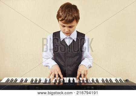 Little cut boy play the keys of the synth