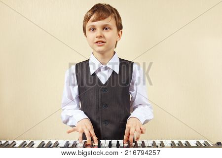 Young cut boy play the keys of the electronic piano