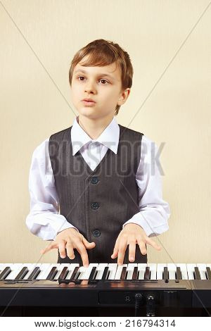 Little pianist in a suit playing the electronic synthesizer