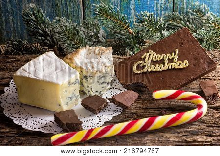 Cambozola Bleu d'auvergne noble gourmet cheeses with blue and white mold and bitter dark chocolate on wooden background branches pine needles and a stick Santa.Christmas card.Merry Christmas