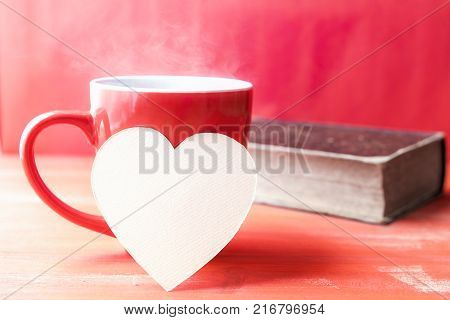 Paper heart on a cup of hot coffee - Greeting card idea with a red cup of hot drink with steam a blank heart-shaped paper note leaned against it and an old book in the background all in a red tone.