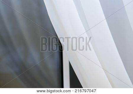 The window in the night covered with a white curtain. The delicate silk curtains at the window. Fabric curtained Windows.