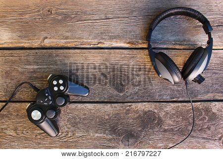Video game controller and headphones on old wooden background. Top view.