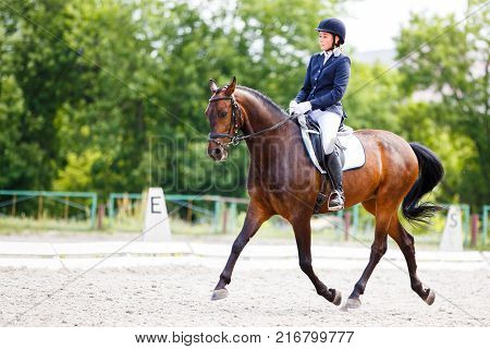 Young rider woman on her course in dressage competition advanced test
