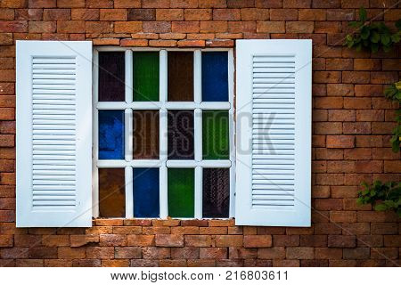 old white wooden window with stained glass on brown brick wall background stone wall with little colorful stained glass window and green leaf on the right side.