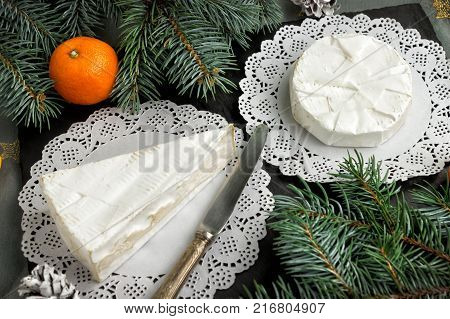 Christmas card concept. Cheeses brie and Camembert with noble white mold. Delicacies for the holidays of Christmas and New year.