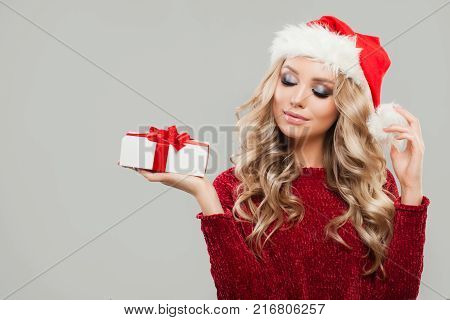Christmas or New Year Portrait of Cute Woman with Christmas Gift on Gray Banner Background. Blonde Fashion Model wearing Santa Hat