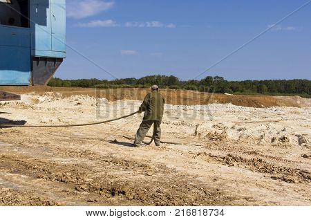 worker dragging heavy electric cabling a large excavator
