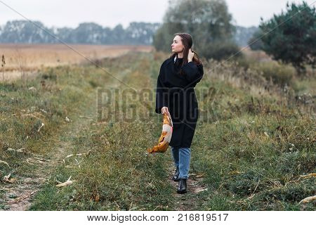 Young woman standing on road in coutryside. Autumn, cloudy weather.