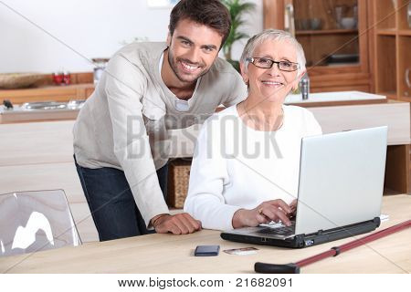Young man helping senior woman with a laptop compute