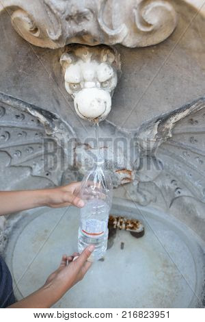 Fountain in Rome with potable water, detail. Boy gets water from a source.