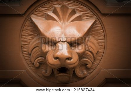 head gold lion knocks on the brown door