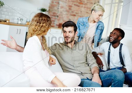 Two happy young couples talking during gathering at home on weekend