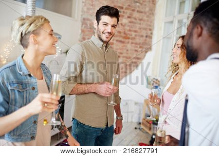 Happy man with flute of champagne surrounded by his friends looking at camera