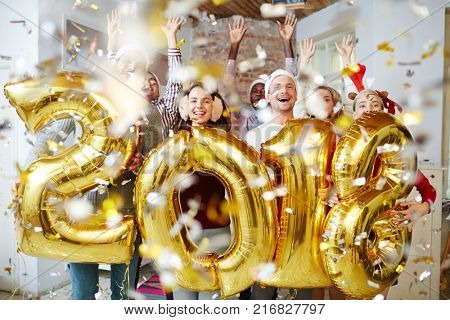 Ecstatic friends with raised hands holding golden balloons in shapes of 2, 0, 1 and 8 in confetti fall