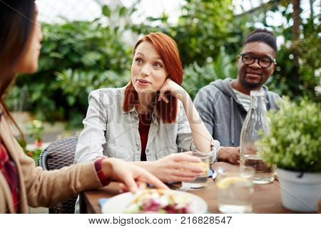 Group of intercultural young companions gathered by breakfast outdoors