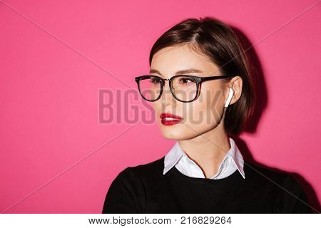 Close up portrait of a confident attractive businesswoman in eyeglasses looking away at copy space isolated over pink background