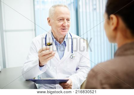 Mature doctor in whitecoat describing new pills in pill-bottle to his patient
