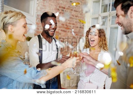 Ecstatic girls and their boyfriends clinking with champagne flutes in confetti fall