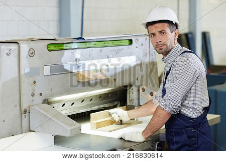 Mid-aged worker in uniform producing technical details on industrial machine
