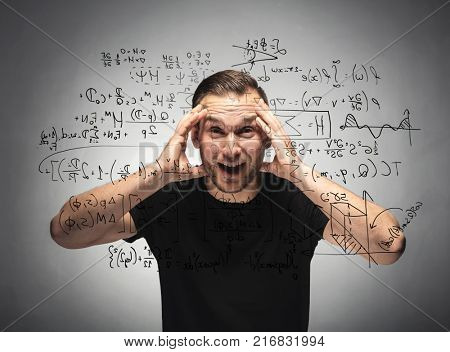 Shocked man looking at mathematical equation. Surprised and astonished man grabbing his head. Student concept.
