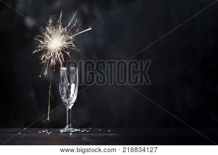 Champagne glass with lit sparkler against a dark background