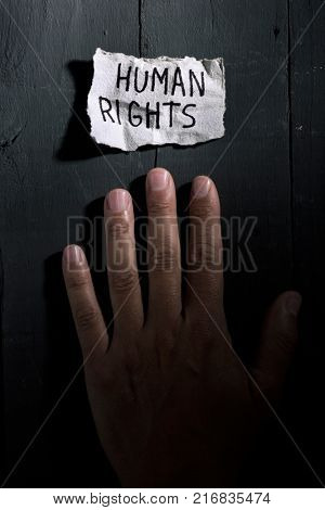 closeup of the hand of a young man and a piece of paper with the text human rights written in it on a rustic background