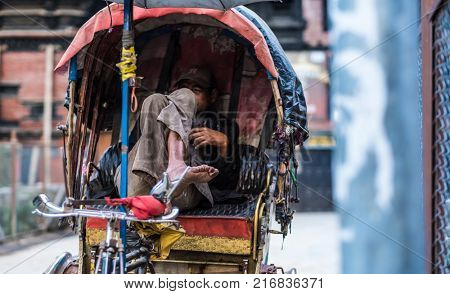 Kathmandu, Nepal - 06 October 2017: Middle-aged rickshaw driver sits with crossed legs in the cabin of his rickshaw and waits for clients.