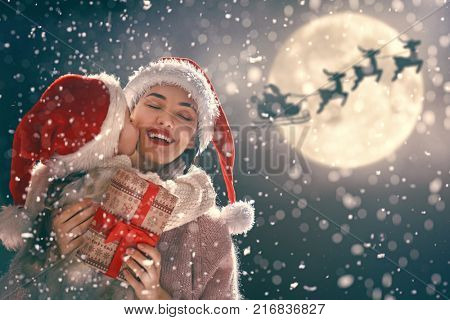 Merry Christmas and Happy Holidays! Mom and daughter are exchanging gifts outdoors. Xmas night. Santa Claus flying in his sleigh against moon sky. Portrait loving family close up.