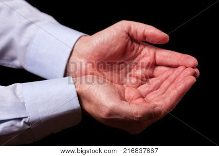Mature male businessman hands together with empty palms up. Concept for man praying, prayer, faith, religion, religious, worship or giving, offering, begging, receiving. Black background.