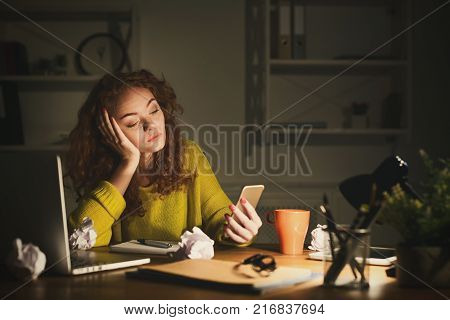 Tired business woman in office at night. Girl working late, holding smartphone, solving a problem at workplace with crumpled papers, gadgets and notepad, copy space. Overworking concept