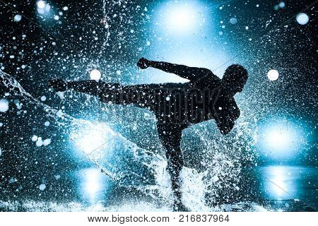 Young man break dancing in club with lights and water. Blue tint colors and dramatic silhouette.