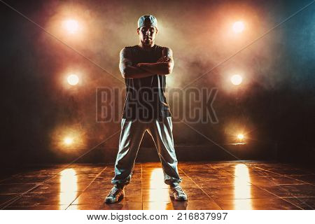 Young cool man break dancer standing in club with lights and smoke. Tattoo on body.