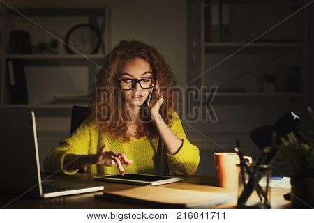 Serious woman working at office at night. Girl in eyeglasses talking on mobile and working on digital tablet at her working place, copy space. Overworking and business consulting concept