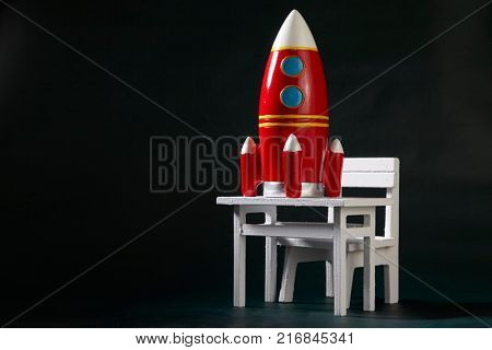 miniature table and chair with toy rocket on the blackboard