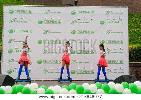 Tyumen, Russia - May 28, 2017: Green marathon of Sberbank on Tura Embankment. Excited young cheerleaders with pompoms cheering on stage