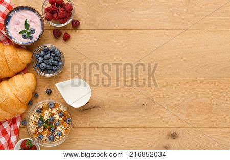Rich continental breakfast background. French crusty croissants, muesli, yogurt, sweet berries and milk jar for tasty morning meals. Delicious start of the day. Top view, copy space on natural wood