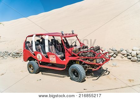 Huacachina Peru - August 2017: Dune buggy at the foot of a large sand dune in Huacachina Peru