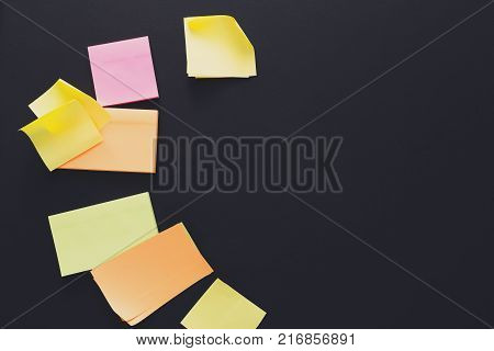 School stationery - many colorful sticky blank notes on black board, top view. Flat lay of office work space with color memo notes with copy space, template, mockup, objects