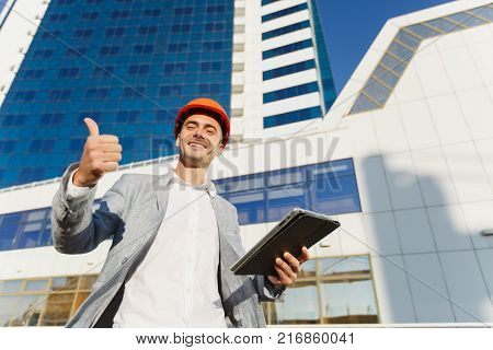 Successful business man in gray suit and protective construction orange helmet with tablet showing thumb up against building in blue color. Engineer in helmet for workers security on office buildings