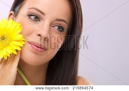 Beautifu youngl woman with yellow flowers on face