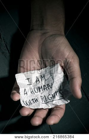 closeup of the hand of a young man with a piece of paper with the text I am a human with rights written in it